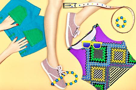 Dames Sexy slanke benen in trendy gumshoes en handen in de zakken op geel background.Set stijlvolle veelkleurige kleding. Bright hipster jeugd zomer look.Fashionable top, shorts, zonnebrillen. copyspace