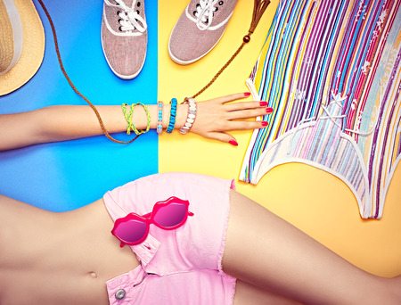 Sexy woman body in fashionable shorts with sunglasses.Handmade bracelets.Set stylish multicolored clothes.Trendy gumshoes.Bright youth beach look. Summer holiday, sea vacation.Blue,yellow background