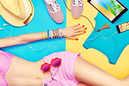 fille sexy: Corps de femme sexy en short � la mode avec sunglasses.Set �l�gant multicolore Smartphone clothes.Trendy, comprim� computer.Bright plage de la jeunesse look. Vacances d'�t�, la mer vacation.Blue, fond jaune