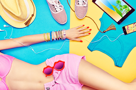Sexy woman body in fashionable shorts with sunglasses.Set stylish multicolored clothes.Trendy Smartphone, tablet computer.Bright youth beach look. Summer holiday, sea vacation.Blue,yellow background Imagens