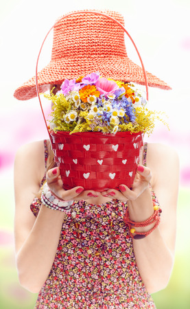 blessedness: Young blonde woman on the summer meadow with red basket of wildflowers. Joyful girl covers her face by orange beach hat. Romantic,  boho style, floral sundress. Bouquet with periwinkle and cornflower.