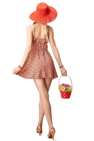 blessedness: Joyful blonde boho woman in floral sundress with red basket of wildflowers on white background. Young girl in orange hat, romantic style, back view. Bouquet with periwinkle, cornflower, summer meadow