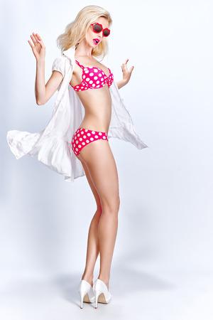 Piękna blondynka seksowna kobieta w czerwonej kropki modny strój kąpielowy i okulary na białym tle, miejsca kopiowania. Playful dziewczyna pinup w prowokacyjne ułożenia. Ciało plaża, szczupła kobiet figure.Summer wakacje, morze stylu