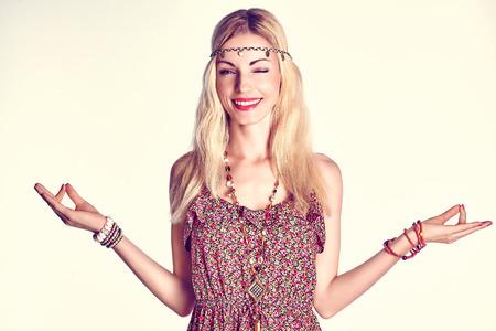 meditates: Beauty portrait of boho woman happy winking and smiling, copy space. Hippie model girl meditates, enjoying relax and harmony. Joyful positive blonde woman in floral fashion sundress doing yoga, fun. Stock Photo