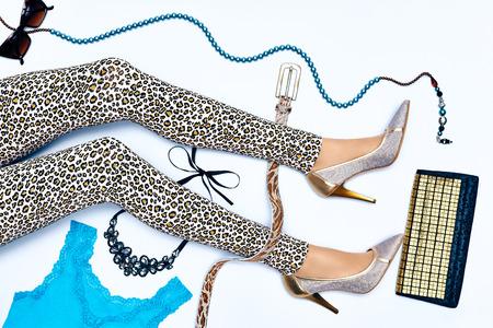 Set van stijlvolle mode kleding, vrouw sexy slanke benen. Levendige glanzende partij accessoires. Glamour ketting, een zonnebril. Trendy top, leggings, schoenen disco look.Unusual, provocerende dame op wit, copyspace.