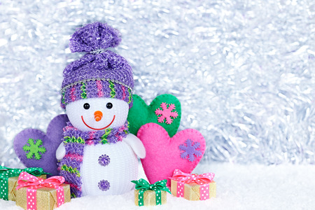 snowmen: New Year 2016. Happy Snowman on snow. Party decoration. Cheerful fun winter holiday on silver background, copyspace. Snowman with multicolored handmade hearts and gift boxes , love concept