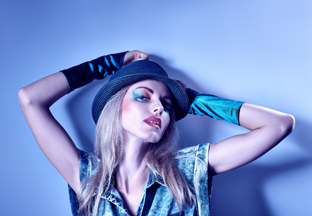 provocative: Fashion portrait of sexy beauty hipster woman in stylish clothes. Unusual creative look. Vivid girl. Provocative emotional playful blonde girl in denim shirt, gloves, hat, make up on blue, copyspace Stock Photo