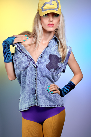 provocative: Beauty fashion sexy hipster woman in stylish clothes. Unusual creative look. Vivid girl. Provocative emotional playful blonde girl in denim shirt, leggings, gloves, yellow cap, make up. Disco punk Stock Photo