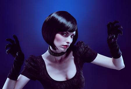 Beauty mode portret sexy brunette vrouw met zijdeachtig bob kapsel in zwarte kleding, handschoenen aan dark.Sensual dame kijkt mysteusly als zwarte kat het dragen van een kraag met spikes.Brown-eyed meisje, make-up