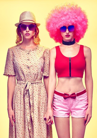 provocative: Beauty fashion sexy hipster woman in stylish clothes, sisters, friends. Unusual party look. Vivid punk girl in sunglasses, hat, with pink afro hairstyle on yellow. Provocative attractive playful lady Stock Photo