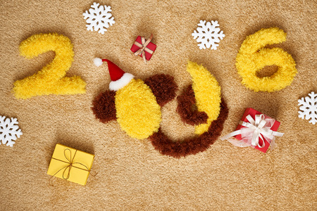 hat new year happy new year festive: New Year 2016. Christmas.Funny monkey in Santa hat with banana,presents. Happy vivid festive still life.Yellow digits handmade. Party decoration, gift box, shaggy unusual holiday card, copyspace