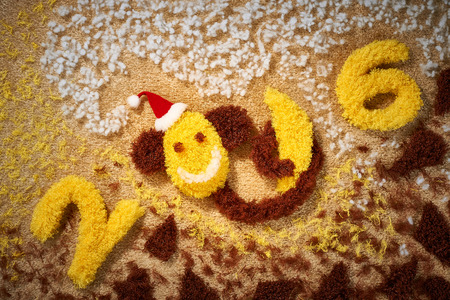 hat new year happy new year festive: New Year 2016. Christmas.Funny monkey in Santa hat with banana. Happy vivid festive still life. Yellow fabric digits handmade. Playful fluffy party decoration.Shaggy unusual holiday card, copyspace