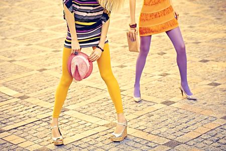 pantimedias: Moda urbana, Belleza, amigos, al aire libre. Para mujer piernas sexy, pantimedias, zapatos elegantes, embragues. Niñas inconformista juguetones en vestidos de moda en adoquín, pose inusual creativo. Fiesta disco Vivid Foto de archivo