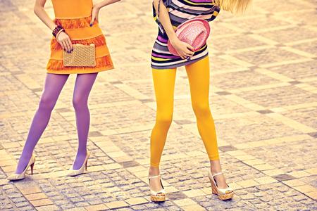 medias veladas: Moda urbana, Belleza, amigos, al aire libre. Para mujer piernas sexy, pantimedias, zapatos elegantes, embragues. Niñas inconformista juguetones en vestidos de moda en adoquín, pose inusual creativo. Fiesta disco Vivid Foto de archivo