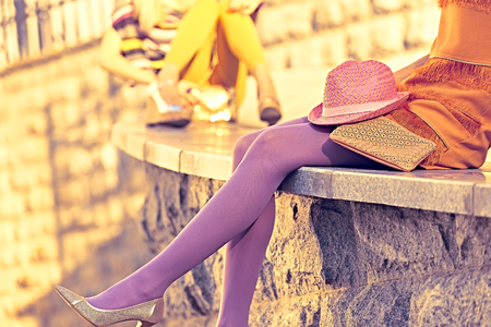 pantimedias: Moda urbana, Belleza, amigos, al aire libre. Para mujer piernas sexy, pantimedias, zapatos elegantes, embragues. Niñas inconformista juguetones en vestidos de moda, fondo de la pared de piedra, creativa inusual. Fiesta de Vivid