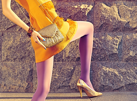 gir: Fashion urban beauty people, woman, outdoor. Playful hipster gir in pantyhose, stylish orange dress with gold clutch, sunny day. Creative unusual pose, stone wall background. Vivid disco party Stock Photo