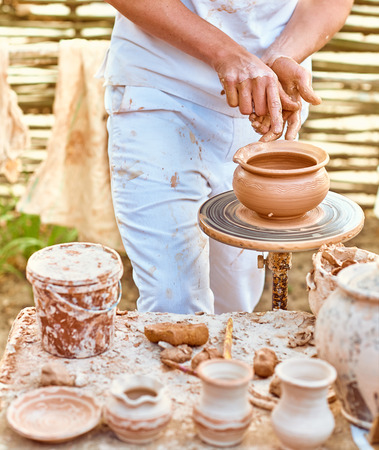 clay craft: Ethnic art, young skilled master creating pot of clay, ceramic, people, outdoors. Ancient historic craft. Process of creating tableware, hobby. Potter machine, village, nature background, summer day Stock Photo