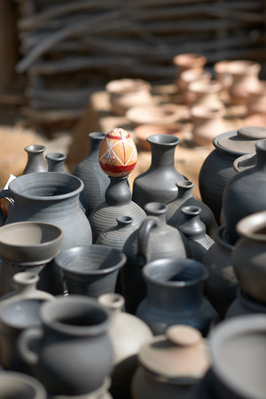 clay craft: Ethnic background texture, art. Pots of clay, ceramic, outdoors. Ancient historic craft. Process of creating tableware, hobby. Village, nature, summer day