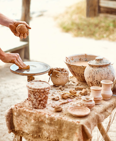 clay craft: Hands of potter do clay pot, skilled master creating ceramic kitchenware, people, outdoors. Ethnic art, ancient historic craft, tableware. Machine, village, rustic background. Nature, summer day Stock Photo