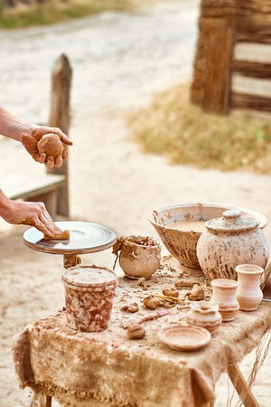 skilled: Hands of potter do clay pot, skilled master creating ceramic kitchenware, people, outdoors. Ethnic art, ancient historic craft, tableware. Machine, village, rustic background. Nature, summer day Stock Photo