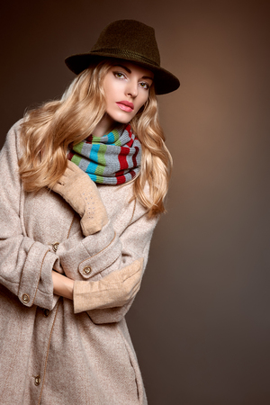 blonde girls: Fashion beauty woman in stylish long coat, hat. Autumn winter model blonde girl with long blonde wavy hair in colored striped scarf, gloves. Unusual creative attractive people. Retro Vintage,copyspace
