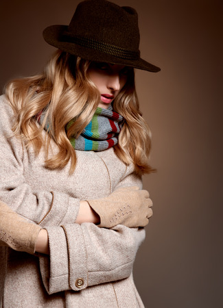 beautiful blonde: Fashion beauty woman in stylish long coat, hat. Autumn winter model blonde girl with long blonde wavy hair in colored striped scarf, gloves. Unusual creative attractive people. Retro Vintage,copyspace
