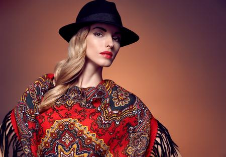rubia: Belleza de la mujer de moda en el elegante sombrero y un chal de color. Modelo del invierno del otoño chica rubia con el pelo largo y ondulado rubio en el patrón pañuelo étnico. Inusual creativa atractiva people.Retro vintage, copyspace Foto de archivo