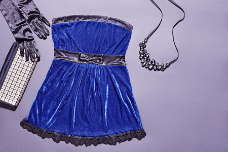 velours: Fashion clothes stylish set, blue mini dress and accessories. Glamor creative, trendy black gloves and shiny clutch, luxury necklaces.  Unusual elegant evening party style, copyspace Stock Photo