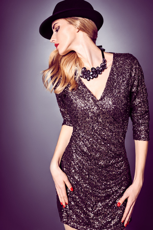 Fashion portrait of sexy beauty woman in stylish sequins dress and black hat. Unusual creative provocative. Emotional playful blonde glamour girl, luxury necklace, evening elegant party style, people Stock fotó