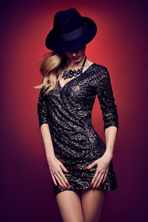 Fashion portrait of sexy beauty woman in stylish sequins dress, black hat. Unusual creative provocative. Emotional playful blonde glamour girl, luxury necklace, evening elegant party on red, people Reklamní fotografie
