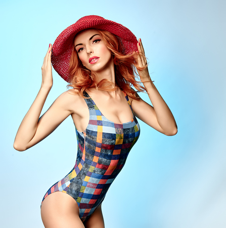 provocative: Beautiful woman in fashionable swimsuit.PinUp playful sexy redhead sensual attractive girl provocative looks, wavy hair, hat.Beach body, slim model, people, copyspace,blue.Summer holiday,sea vacation Stock Photo