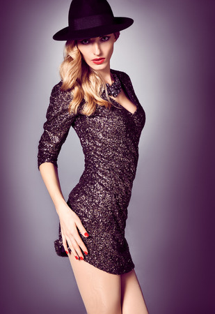 black hat: Fashion portrait of sexy beauty woman in stylish sequins dress and black hat. Unusual creative provocative. Emotional playful blonde glamour girl, luxury necklace, evening elegant party style, people Stock Photo