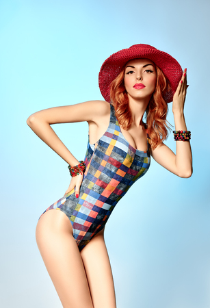 sexy redhead: Beautiful woman in fashionable swimsuit.PinUp playful sexy redhead sensual attractive girl provocative looks, wavy hair, hat.Beach body, slim model, people, copyspace,blue.Summer holiday,sea vacation Stock Photo