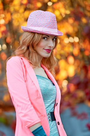 gir: Fashion urban beauty people, smiling woman, outdoor. Playful glamor hipster redhead gir in stylish hat, vivid jacket and gloves. Sunny day, autumn orange bokeh. Creative unusual, park, lifestyle