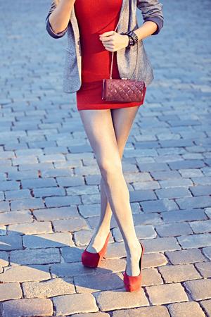 medias veladas: Moda, Belleza urbanas, mujer, muchacha del encanto inconformista outdoor.Playful en el vestido rojo pantyhose.Stylish, chaqueta brillante, zapatos, embrague de moda, day.Creative soleado inusual, piedra de pavimentación, lifestyle.Vivid discoteca Foto de archivo