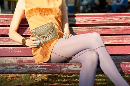 medias veladas: Moda, Belleza urbanas, mujer, al aire libre. Juguetón muchacha del encanto inconformista en el banco en pantimedias, vestido elegante color naranja con el embrague de oro, día soleado. inusual postura creativa, estilo de vida. partido de disco Vivid Foto de archivo