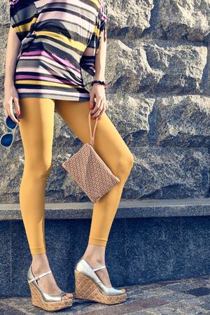 pantimedias: Moda, Belleza urbanas, mujer, al aire libre. Juguetona ni�a glamour inconformista en pantimedias, vestido de los zapatos con estilo, embrague, gafas de sol, d�a soleado. Creativa inusual, fondo de la pared de piedra, disco lifestyle.Vivid Foto de archivo