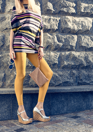 medias veladas: Moda, Belleza urbanas, mujer, chica rubia glamour inconformista outdoor.Playful en pantimedias, zapatos con estilo, vestido, embrague, gafas de sol de fondo de la pared creativa inusual, piedra, soleado, lifestyle.Vivid discoteca Foto de archivo