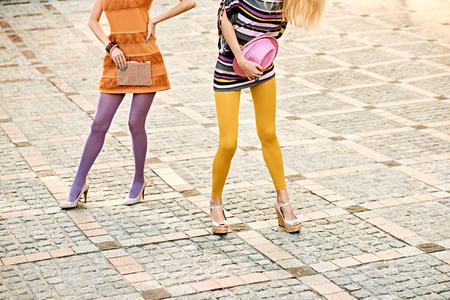 medias veladas: Moda urbana, Belleza, amigos, outdoor.Womens piernas sexy, pantimedias, zapatos elegantes, embrague, niñas inconformista hat.Playful en vestidos de moda en adoquín, pose.Vivid inusual creativo discoteca estilo de vida