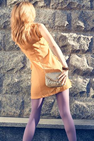pantimedias: Moda poblaci�n urbana de belleza, mujer, encanto inconformista pantimedias chica pelirroja outdoor.Playful, vestido elegante color naranja con el embrague de oro, day.Creative soleado inusual, fondo de la pared de piedra, lifestyle.Vivid discoteca