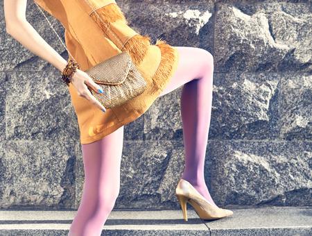 pantimedias: Moda urbana gente belleza, mujer, chica inconformista glamour outdoor.Playful en pantimedias, vestido naranja con estilo de moda embrague oro, day.Creative soleado inusual, fondo de la pared de piedra, disco lifestyle.Vivid