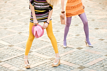 pantimedias: Moda urbana, Belleza, amigos, outdoor.Womens piernas sexy, pantimedias, zapatos elegantes, embrague, niñas inconformista hat.Playful en vestidos de moda en adoquín, pose.Vivid inusual creativo discoteca estilo de vida