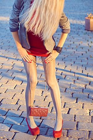 pantimedias: Moda, Belleza urbanas, mujer, outdoor.Playful muchacha del encanto inconformista pantyhose.Stylish vestido rojo, chaqueta brillante, embrague de moda, day.Creative soleado inusual, allanando el fondo de piedra, partido lifestyle.Vivid