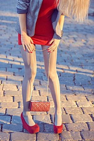medias veladas: Moda, Belleza urbanas, mujer, outdoor.Playful muchacha del encanto inconformista pantyhose.Stylish vestido rojo, chaqueta brillante, embrague de moda, day.Creative soleado inusual, allanando el fondo de piedra, partido lifestyle.Vivid