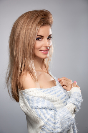 provocative woman: Beauty fashion portrait woman in stylish warm knitted sweater smiling. Sensual attractive pretty blonde sexy model girl, shiny straight hair. Unusual creative provocative. Emotional playful people