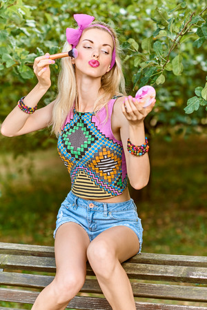 summer beauty: Beauty stylish playful woman primping with mirror on bench, park, people, outdoors.Attractive hipster happy pretty blonde girl with bow, fashionable top, denim shorts. Relax in summer garden,lifestyle