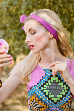 summer beauty: Beauty portrait stylish playful woman primping with mirror in park, people, outdoors. Attractive hipster happy pretty blonde girl with bow, fashionable top. Relax in summer garden, lifestyle, bokeh
