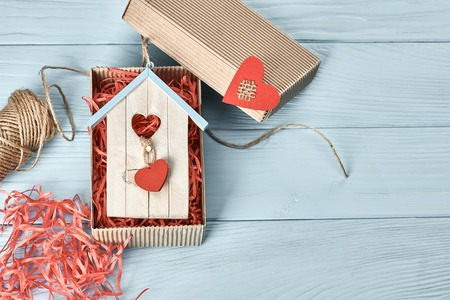 Valentines Day. Love red hearts, souvenir house in gift box, twine. Vintage retro romantic style. Unusual creative greeting card, wooden blue background, copyspace, toned