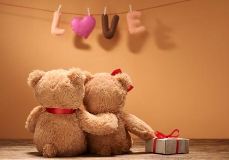 Valentijnsdag. Word Love heart. Paar Teddy Bears in omhelzing, het koesteren, datum. Handgemaakt, gft doos. Vintage retro romantische stijl. Ongebruikelijke creatieve wenskaart op hout. Familie, huwelijk en vriendschap