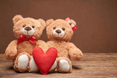 Valentijnsdag. Liefde hart. Paar Teddy Bears in omhelzing, knuffelen. Handgemaakte rood hart, lint, boog. Vintage retro romantisch style.Unusual creative wenskaart op hout. Familie, huwelijk en vriendschap